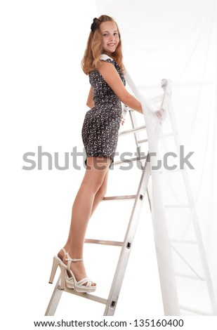 The young beautiful girl goes upward on a ladder on a white background - stock photo