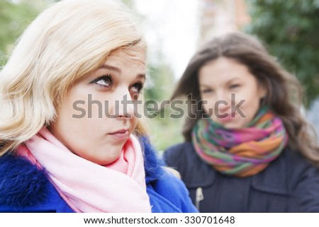 The young beautiful girl has a conflict on the street  in the cold - stock photo