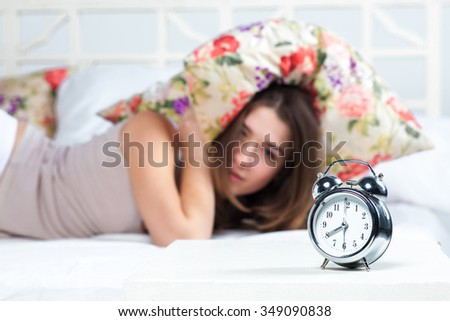 The young beautiful girl in bed. The clock service is in the foreground - stock photo