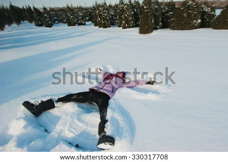 The young beautiful girl in bright clothes is sitting in the snow, laughing, winter holidays
