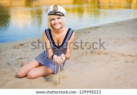 The young beautiful girl strews sand from her hand on a beach