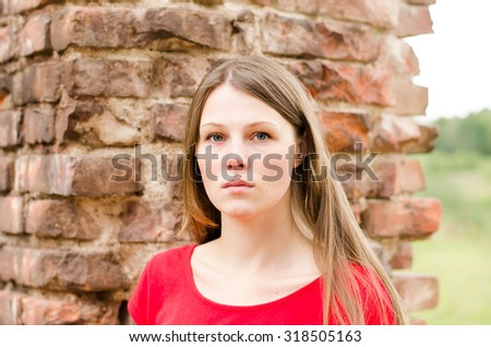 The young beautiful girl with freckles and red dress standing near the wall of red brick
