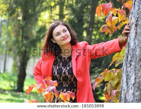 The young beautiful girl with long hair and blue eyes in city park among bright foliage