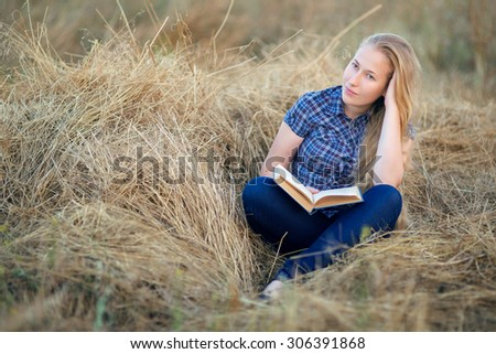 The young beautiful girl with long hair reads the book sitting on hay open-air, the blonde in an outer entrance hall a shirt and jeans outdoors. - stock photo