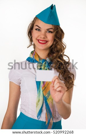 The young, beautiful stewardess holds a card on a white background