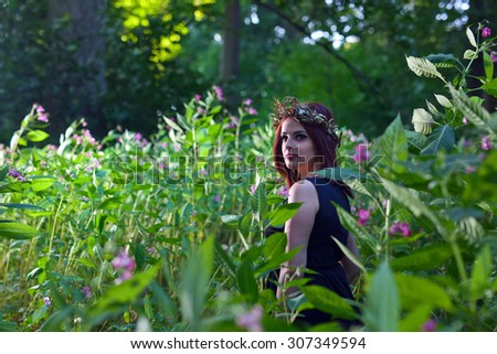 The young beautiful witch in dark forest  - stock photo