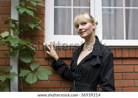The young beautiful woman at a country house wall