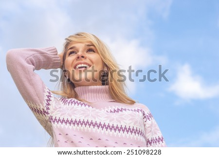 The young beautiful woman has a rest, having combined hands behind head, and smiles, against dark blue sky. - stock photo