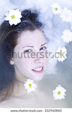 the young beautiful woman in a bath with milk and flowers
