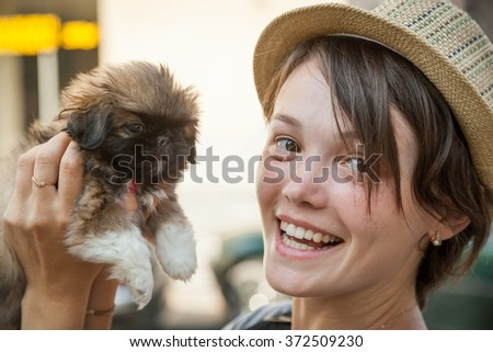 the young beautiful woman in a hat holds a little puppy in hand