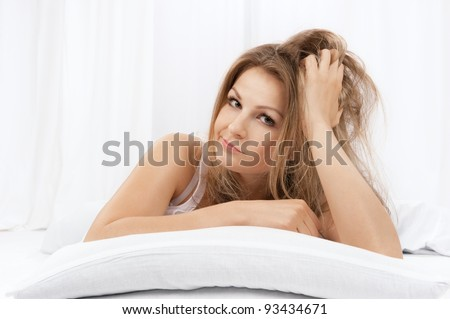 The young beautiful woman in bed on white