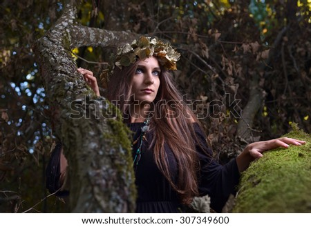 The young beautiful woman in dark forest  - stock photo