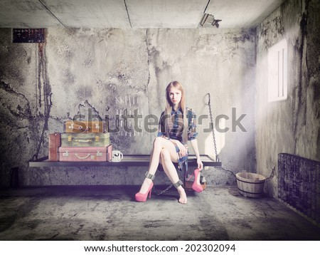 the young beautiful woman in jail with her baggage. Concept - stock photo