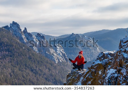The young beautiful woman in mountains has a rest in the winter at the weekend