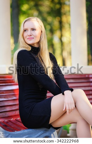 The young beautiful woman on a bench in the park - stock photo