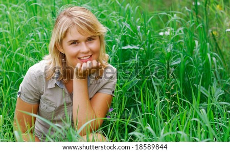 The young beautiful woman sits in a grass and smiles.