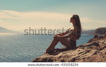 the young, beautiful woman sits on the seashore