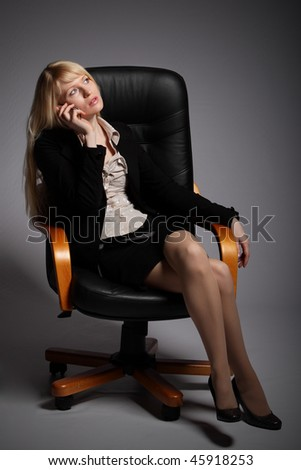 The young blonde the business woman sits in armchair and holds a phone