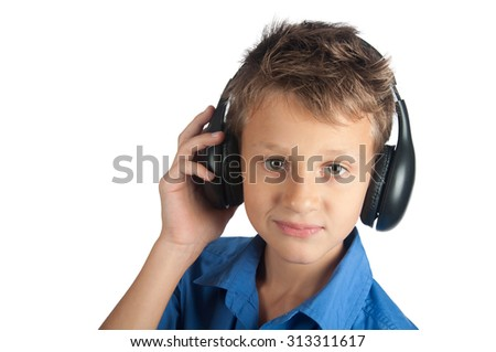 The young boy in blue shirt is smiling and listening to music in black headphones isolated on white background