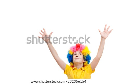 The young boy in clown wig hands up, isolated on white background - stock photo