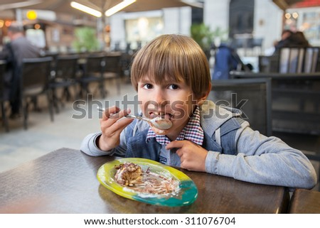 The young boy is eating profiterole with ice-cream and chocolate - stock photo