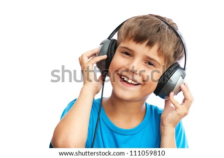 The young boy is laughing and holding headphones - stock photo