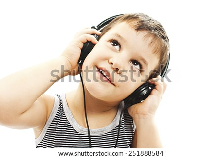 The young boy is smiling and listening to music, looking up. Isolated on white background