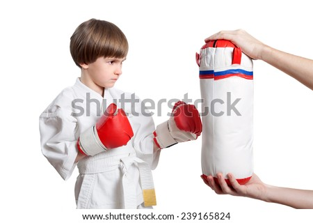 The young boy is training to kick punchbag - stock photo
