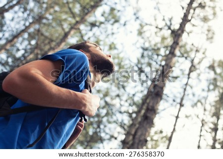 The young boy with a backpack stand in forest - stock photo