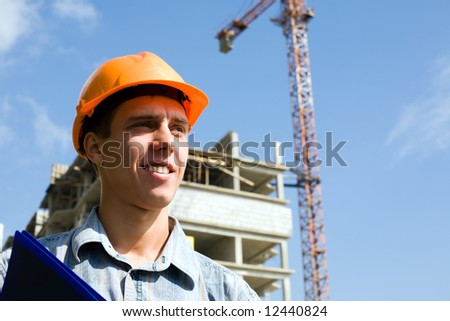 The young builder inspector on a background of building object. - stock photo