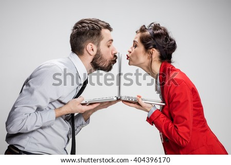 The young businessman and businesswoman with laptops kissing screens on gray background - stock photo