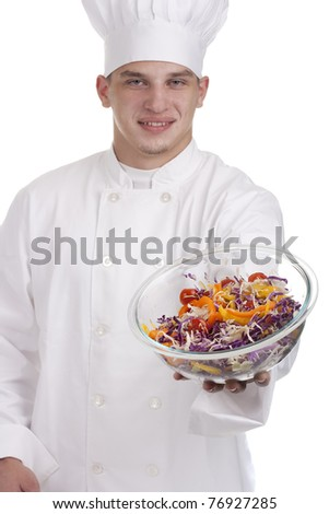 The young chef in uniform and chef's hat stretches salad in a bowl.
