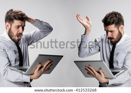 The young confused and frustrated man with his laptop computer - stock photo