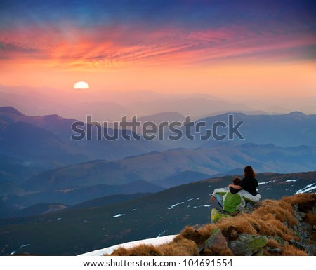 The young couple meets the sunrise in the mountains - stock photo