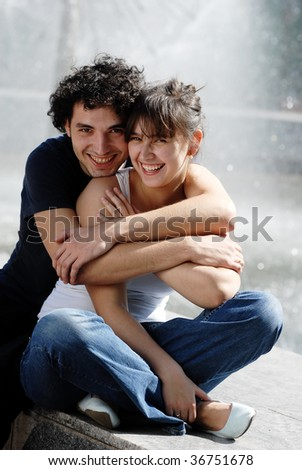 The young couple smiling in the street - stock photo