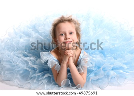 The young fine  girl (child) in a blue dress lays on a white background - stock photo