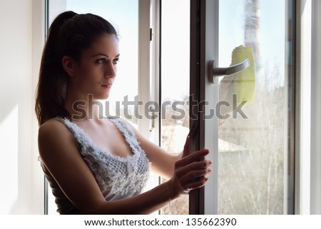 The young girl carefully washes and cleans a window