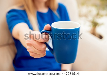 The young girl drinks coffee. In the office - stock photo