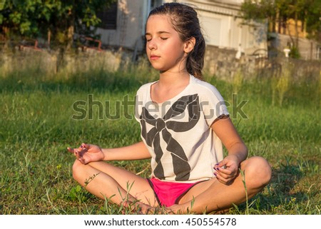 The young girl engaged in yoga, gymnastics on the grass. Healthy lifestyle. - stock photo