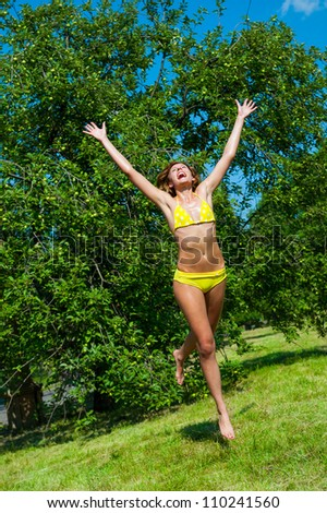 The young girl in a bathing suit jumping in park - stock photo