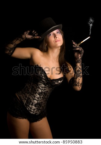 The young girl in a black corset smoke cigarette and looks up - stock photo