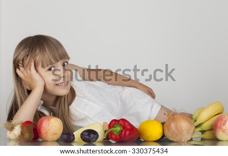 The young girl in a white dress with fruits and vegetables on a white background