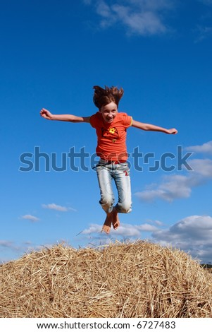 The young girl jumps on a bale of a straw on the blue sky  background