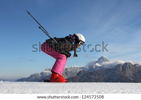 The young girl on skis in the background of mountains covered with snow - stock photo