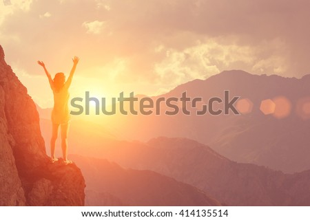 The young girl raised her arms up to the sun on a background of mountains and sky with clouds - stock photo