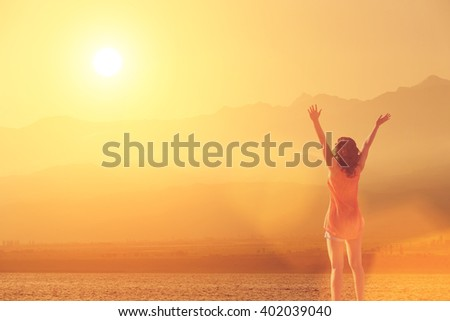 The young girl raised her arms up to the sun on a background of mountains, sea and sky with clouds - stock photo