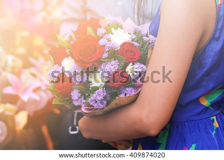 The young girl was carrying a brightly colored flowers  for someone. Close-concept. - stock photo