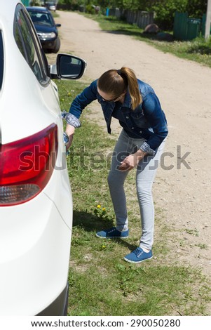 the young girl washes with hands the white car - stock photo