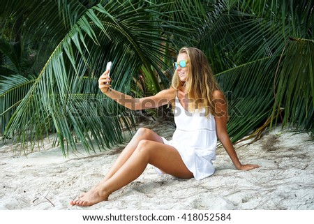 The young girl with a fair hair, takes a selfie, being in the tropical country, the girl in a hammock going on the beach lies in a hammock, - stock photo