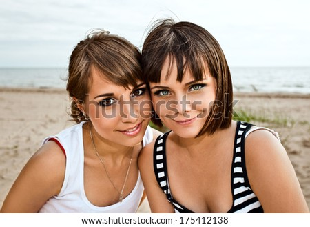 The young girlfriends on a sea beach